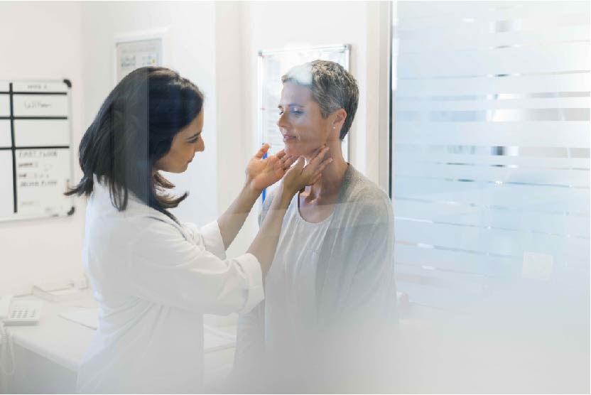 a doctor examines a patients thyroid